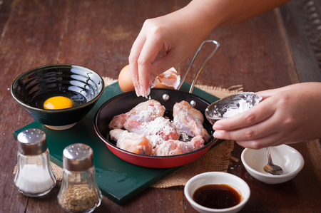 corn flour: Preparation for cooking in home kitchen. Woman right hand put corn flour into fry pan to mix with chicken wings Stock Photo