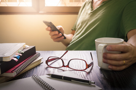 Glasses put down on table beside notebooks and pen while young freelance worker using smart phone and holding coffee cup in morning time on work day, Working at home concept Stock Photo - 56818308