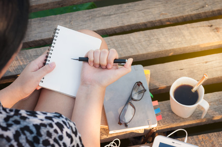Young hipster woman writing journal on small notebook while sitting on wood bridge in morning time on weekend