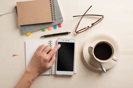blank space: Young man touching on smartphone screen beside notebooks, glasses, and coffee cup on wood table in morning time