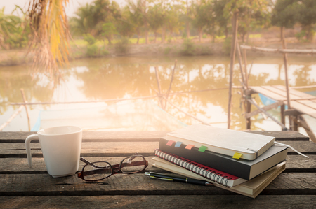 Pen, opened notebook, glasses, and coffee cup on outdoor wood table in morning time on weekend. Freelance business working concept