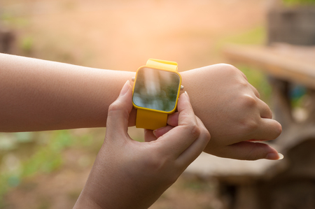 e systems: Young woman put button on yellow smartwatch with nature blurry background in morning time,