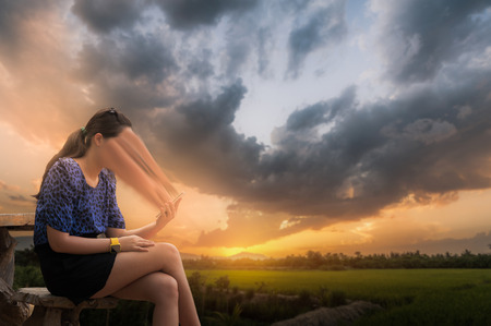 Abstract scene of young woman using her smartphone seriously while sitting outdoor on wood chair in morning time on weekend with blurry nature background. Phone addiction abstract concept. Stock Photo