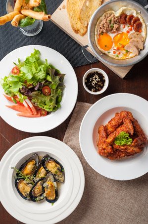 korean salad: Top view of modern cuisine set including spring rolls, pan fried egg, Korean style deep fried chicken, baked mussels, and Japanese crab stick salad on wood table in restaurant