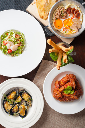 korean salad: Top view of modern cuisine set including spring rolls, pan fried egg, Korean style deep fried chicken, baked mussels, and sunflower sprout salad on wood table in restaurant Stock Photo