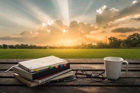 펜, 노트북, 안경 및 커피 컵 흐린 배경 자연보기 주말 아침 시간에 야외 나무 테이블에 열립니다. 프리랜서 비즈니스 작업 개념