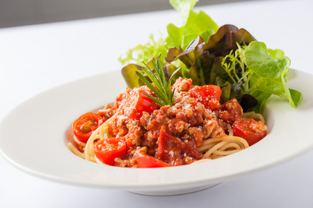 garnished: Italian style pasta red sauce with tomato and minced pork garnished with vegetables Stock Photo