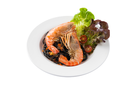 Front view of Japanese style black pasta with Thai river prawn and vegetables in ceramic dish isolated on white background