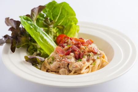 macarrones: la pasta carbonara con tocino y verduras en el plato de cerámica Foto de archivo