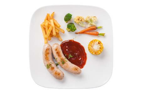 side dishes: Top view of Modern European style grilled sausage with ketchup and side dishes including grilled vegetables and french fries in ceramic dish isolated on white background