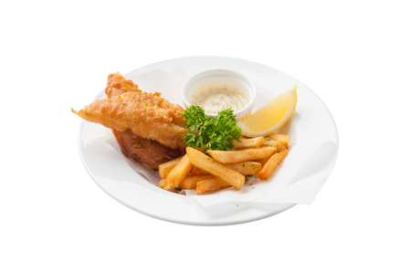 fish isolated: Front view of Traditional British style fish and chips including deep fried cod, french fries, lemon, and tartar sauce in ceramic dish isolated on white background Stock Photo