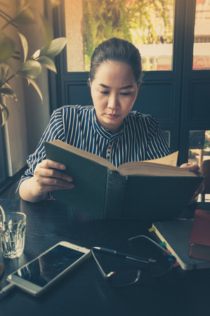living wisdom: Sunday morning lifestyle scene of young hipster asian woman reading book in cafe with. Weekend activity or hobby concept with vintage filter effect Stock Photo