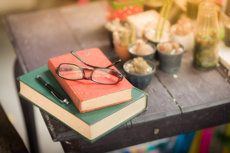 Glasses with books and pen on wood table in morning time. weekend lifestyle concept Stock Photo