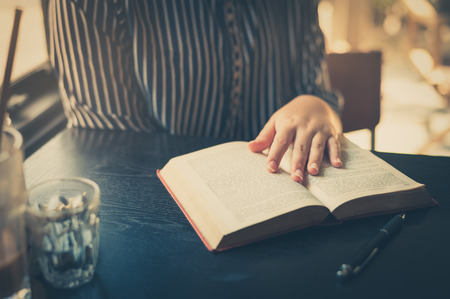 erudition: Sunday morning lifestyle scene of young hipster asian woman reading book in cafe with. Weekend activity or hobby concept with vintage filter effect Stock Photo