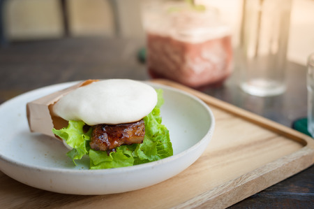 gua: Pork bun (Gua bao in Taiwan) with Thai style spicy grilled pork and vegetable on wood table in cafe with watermelon smoothie in blurry background. Creative and contemporary recipe concept Stock Photo