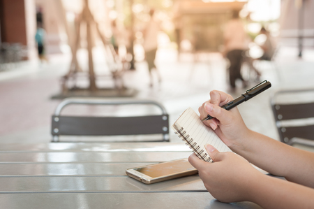 Urban lifestyle scene of woman hand writing on notebook at coffee shop. Freelance worker lifestyle Stock Photo