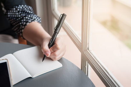 Left-handed woman holding pen while writing on small notebook beside window. Freelance journalist working at home concept.