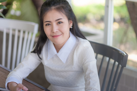 Young attractive Asian woman smiling while sitting in cafe. Cute girl with hapiness feeling concept