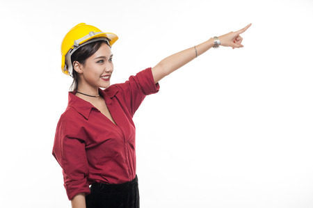 Asian woman engineer in red shirt and yellow safety cap pointing front with happy emotion. People gesturing in business and enginerring concept