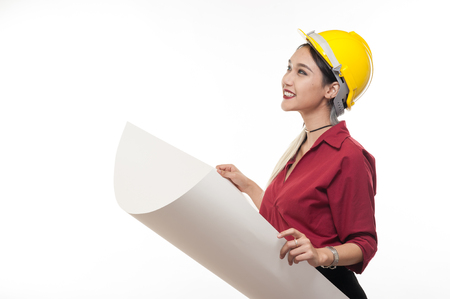 Young Asian woman architect with red shirt and yellow safety helmet smiling while reading blueprints. Industrial occupation people concept Banque d'images