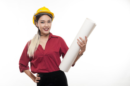 Young Asian woman architect with red shirt and yellow safety helmet smiling while carrying blueprint papers. Industrial occupation people concept Banque d'images