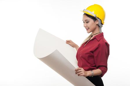 Jeune architecte femme asiatique avec une chemise rouge et un casque de sécurité jaune souriant tout en lisant des plans. Concept de personnes occupation industrielle Banque d'images