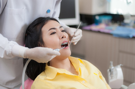 Female patient in oral checkup with male dentist in dental clinic. Health care and maintenance with expert concept