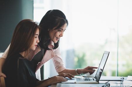 Trabajadores de negocios asiáticos jovenes que trabajan junto con la computadora portátil en la oficina. Concepto de lluvia de ideas y trabajo en equipo de inicio de negocios