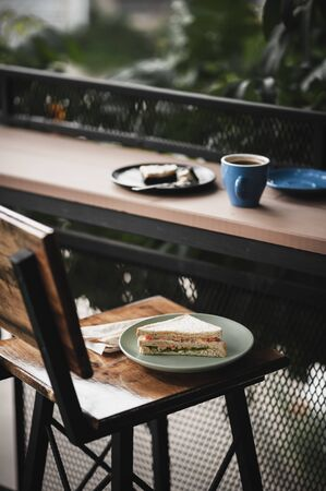 Abstract scene of breakfast meal set including tuna sandwich, hot long black coffee, and brownie cheese cake on outdoor wood bar.