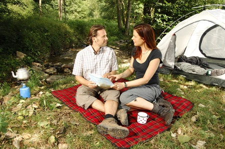 picknic: Couple discussing hiking plans in front of a tent