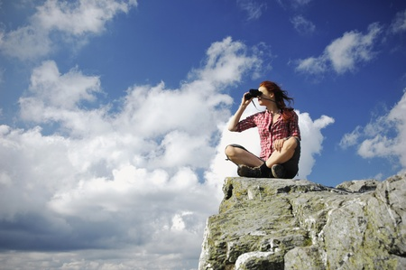 Woman sitting on a mountain looking with binocular into the distance Standard-Bild