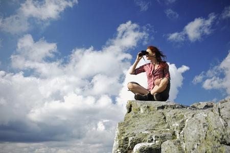 Vrouw zitten op een berg kijken met verrekijker in de verte