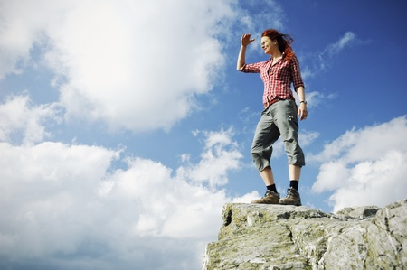 Redheaded woman standing on a mountain and gazing in the distance photo