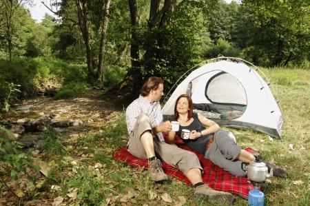 Çift, bir çadırın önünde rahatlatıcı ve çay içme
