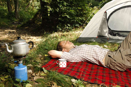 picknic: Man resting in front of a tent, teacup on a checkered blanket