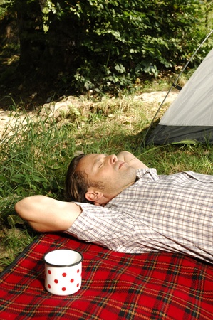 Man resting on a checkered blanket, cup beside him