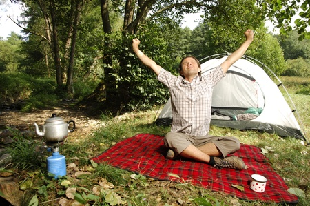 picknic: Man stretching in front of a tent Stock Photo