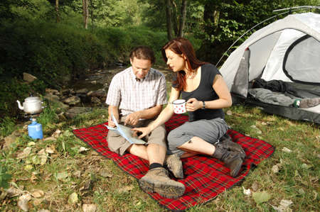 Couple discussing hiking plans in front of a tent