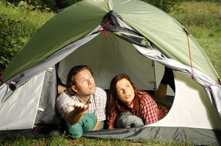 picknic: Couple lying in tent checking the weather