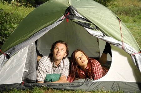 picknic: Couple lying in tent, checking the weather outside
