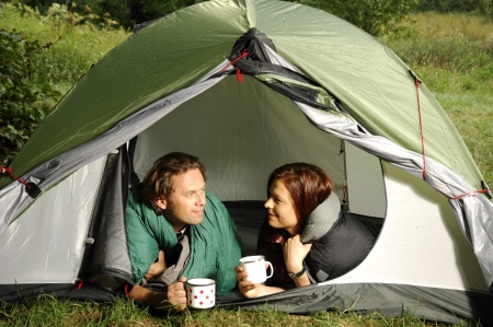 picknic: Couple lying in tent and having some morning coffee