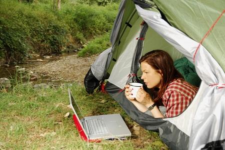 Vrouw met laptop liggend in een tent