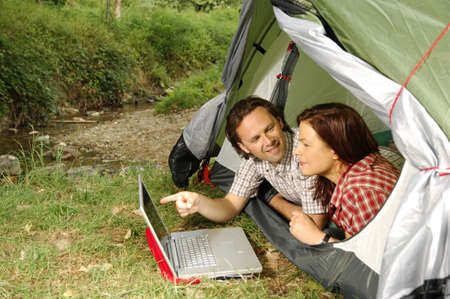 Couple with laptop lying in a tent, man pointing towards screen