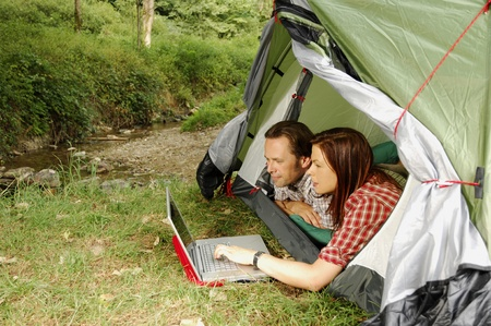 Couple with laptop lying in a tent
