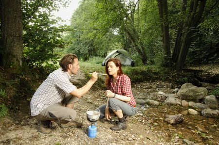 Couple preparing food outdoors