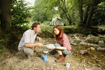 Couple preparing food outdoors photo