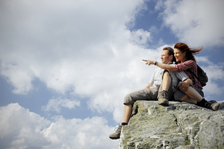 Two people sitting on top of a mountain, woman pointing towards something in the distance photo