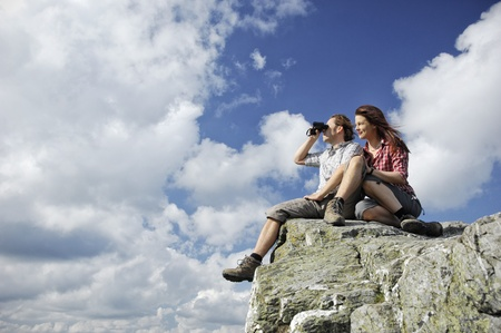 Two people sitting on top of a mountain, man looking with binocular into the distance photo