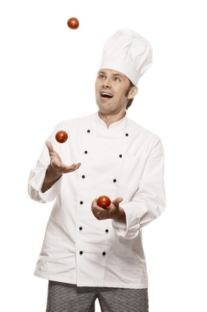 toque blanche: Chef juggling with tomatos Stock Photo