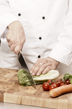 toque blanche: Chef cutting vegetables on a cutting board